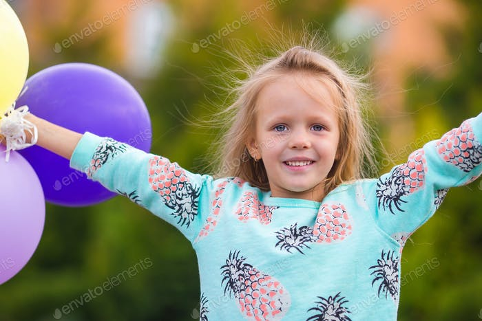 Portrait of happy little girl playing with balloons outdoors