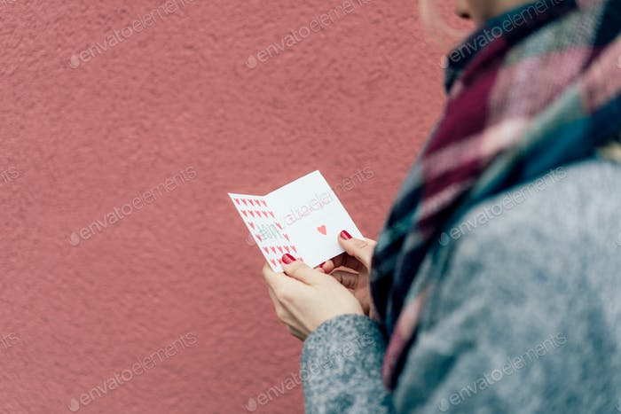 Valentine's card in female hands. Text I LOVE YOU