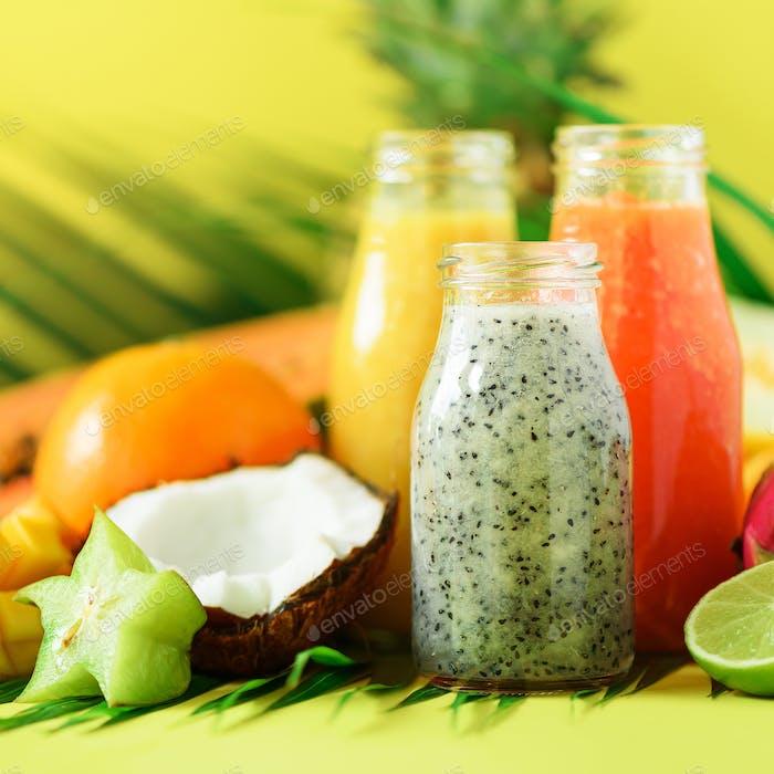 Saftige Papaya und Ananas, Mango, Orangenfrucht-Smoothie in Gläsern auf gelbem Hintergrund. Detox, Sommer