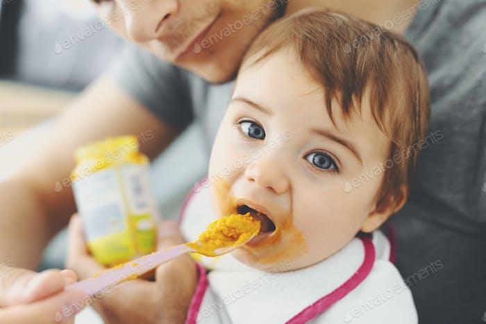 Dad feeding baby boy with spoon