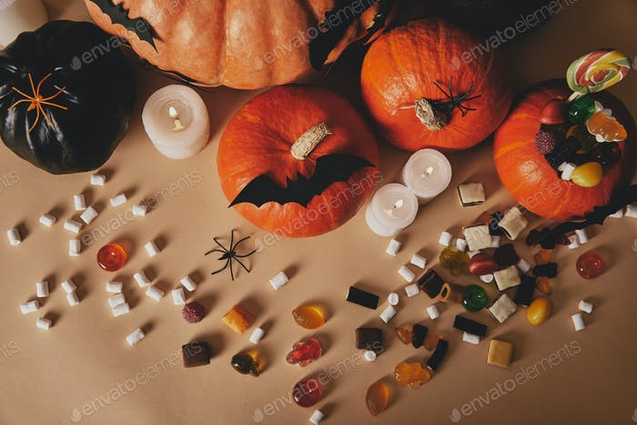 top view of pumpkins, jelly candies and paper bats on table, halloween concept