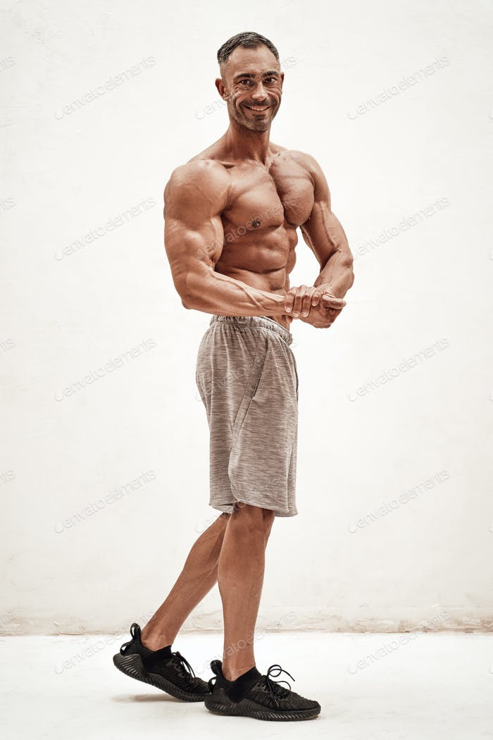 Shirtless sporty caucasian male isolated on a white concrete background showing athletic body