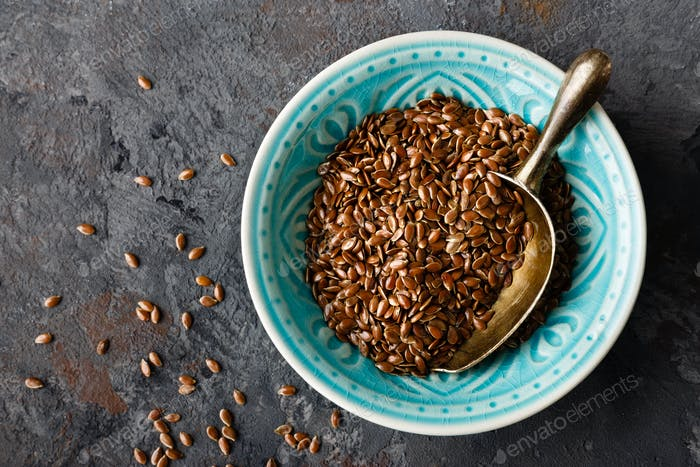 Flax seeds in bowl on dark background closeup top view