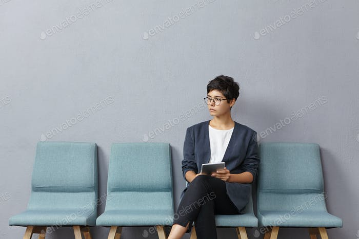 Horizontal portrait of young attractive woman being in anticipation of meeting with potential partne