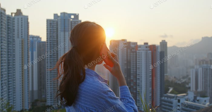 Woman talk to cellphone in the background of the city under sunset time