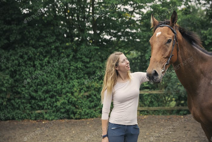 Woman patting a large bay thoroughbred horse horse in a paddock.