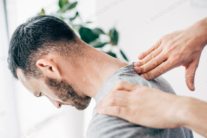Cropped view of chiropractor massaging male patient neck in massage cabinet at clinic
