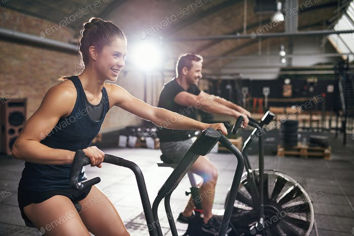 Two people having workout on cycling machines