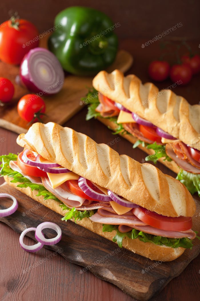 long baguette sandwich with ham cheese tomato lettuce