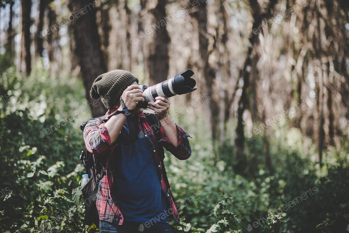 Young photographer taking photo in the forest