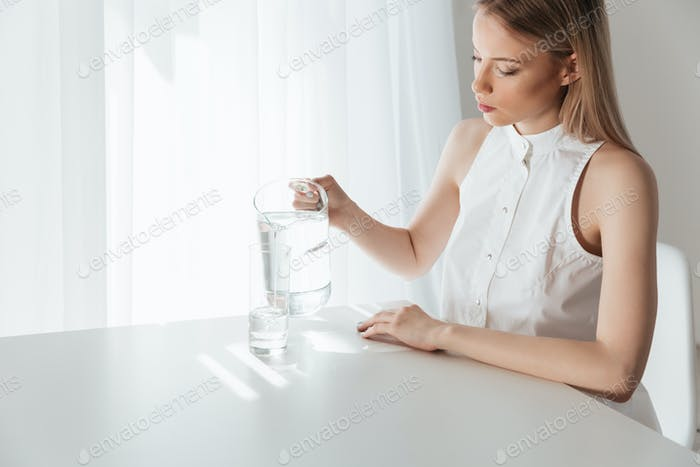 Serious blonde lady sitting indoors near water jug