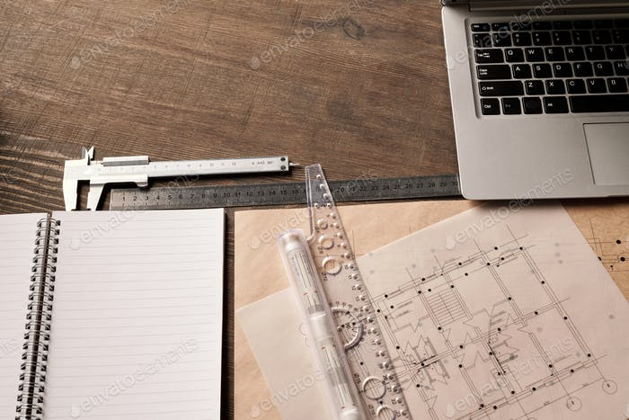 Laptop keypad, rulers and handtool, open copybook surrounded by blueprints
