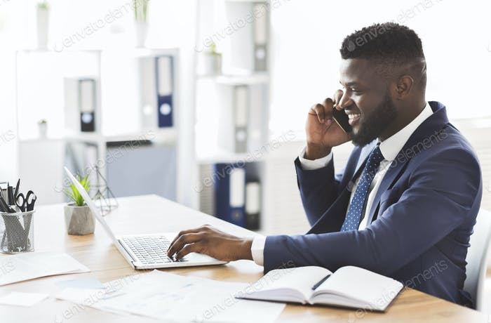 Cheerful young entrepreneur having conversation with business partner by cellphone
