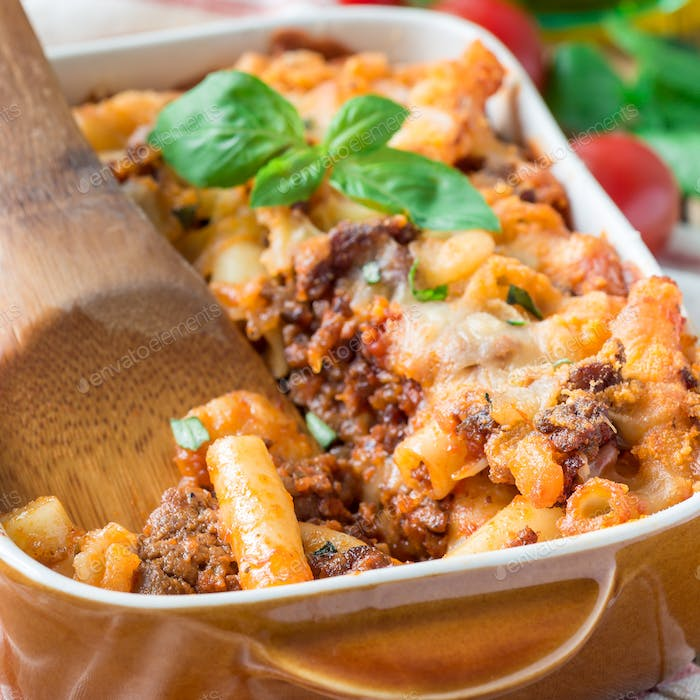 Ziti bolognese in baking dish, pasta casserole with minced meat, tomato sauce and cheese, square