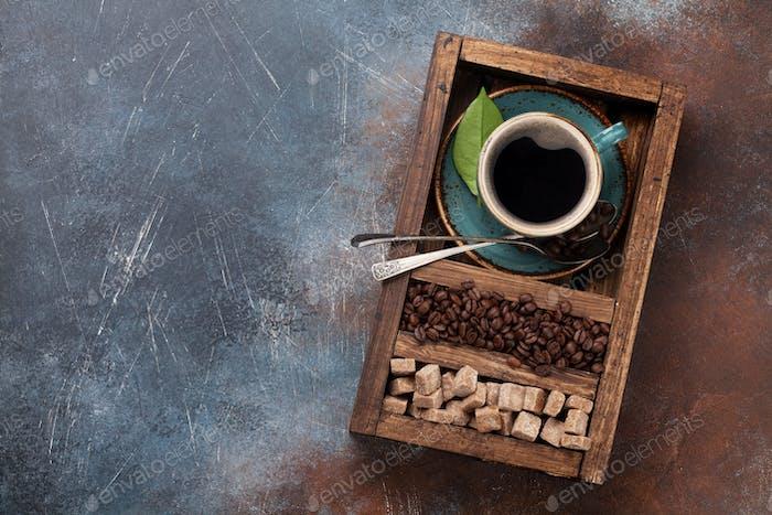 Kaffeetasse, geröstete Bohnen und brauner Zucker
