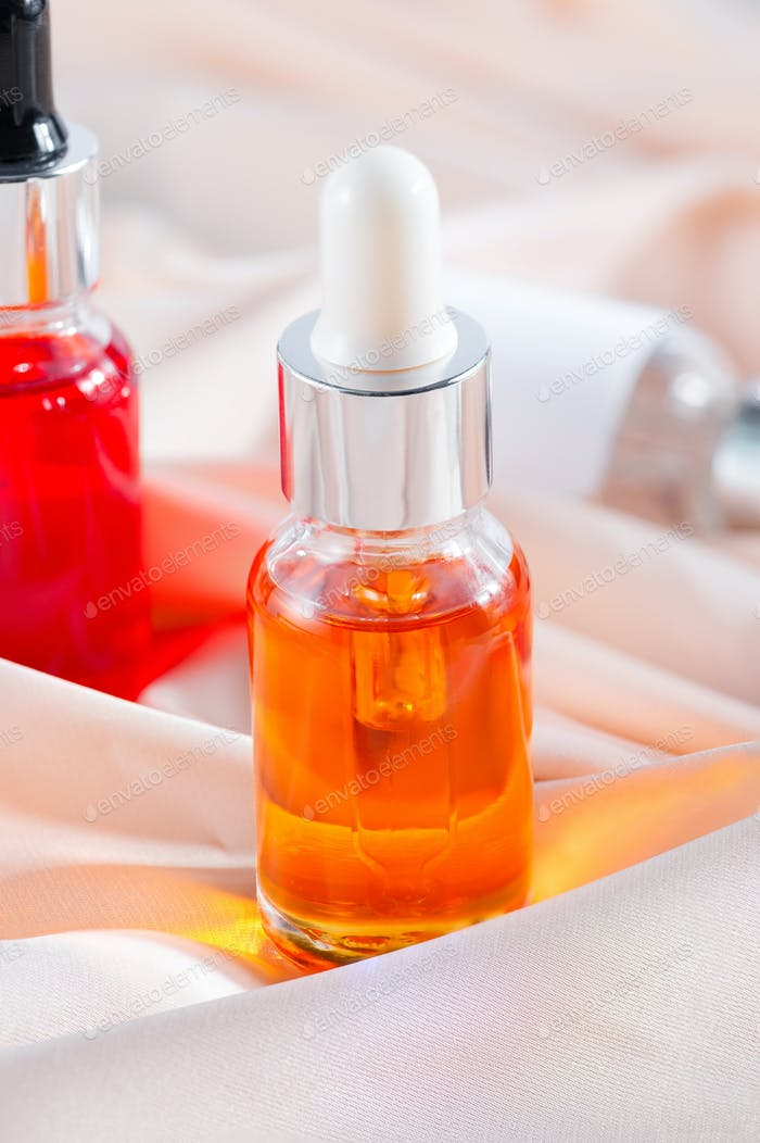 Close-up serum essence in glass bottle on beige silk background
