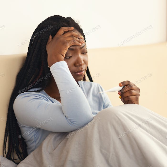 Black Woman Holding Thermometer Having Fever And Headache In Bedroom