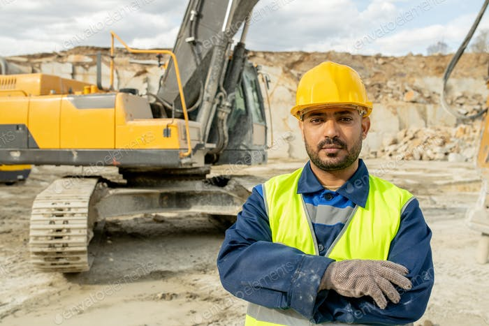 Serious builder in workwear crossing arms on chest