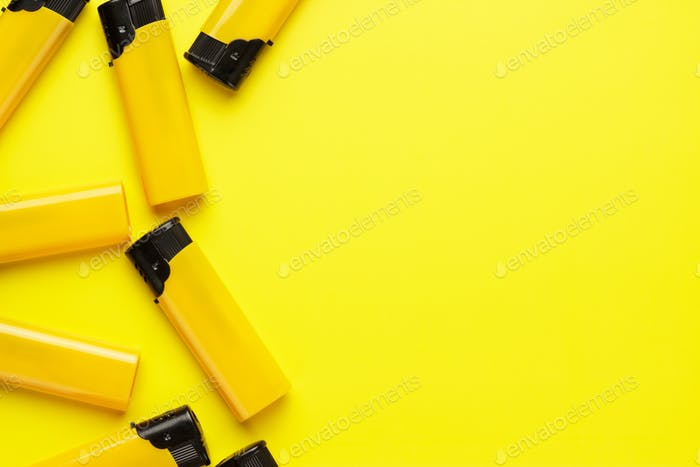 plastic lighters on yellow background