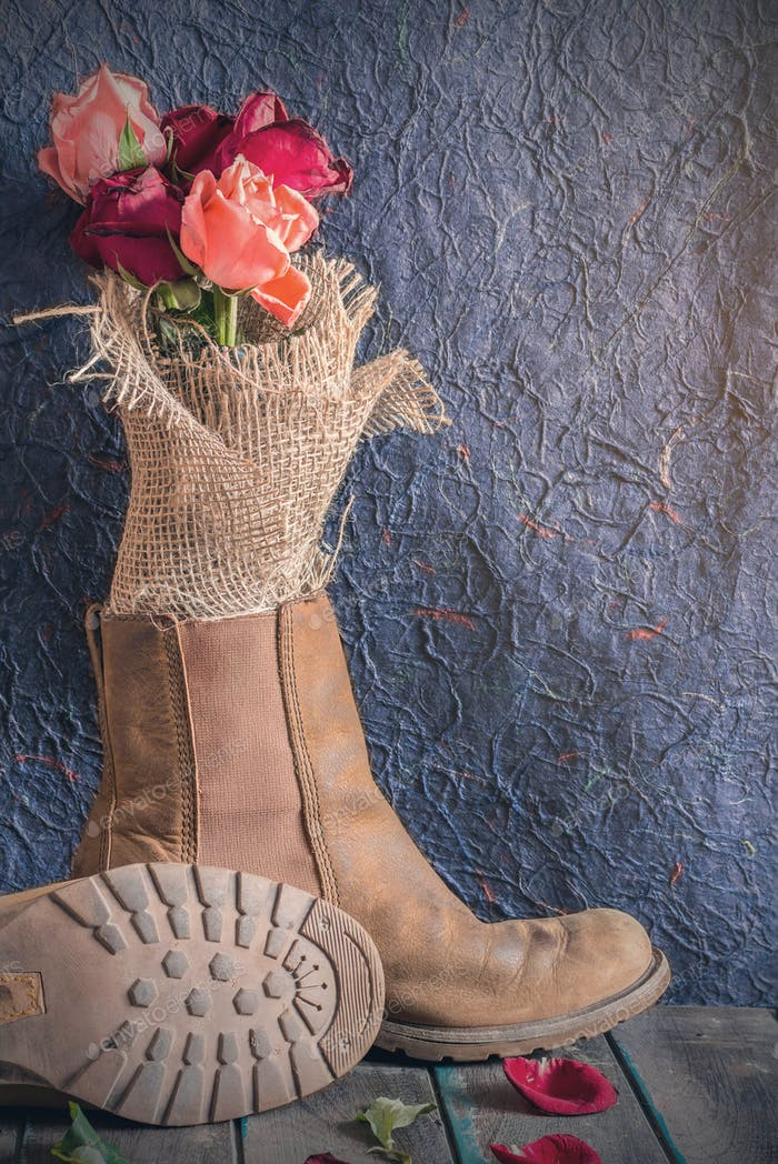 Rosen in Schuhen auf Holz