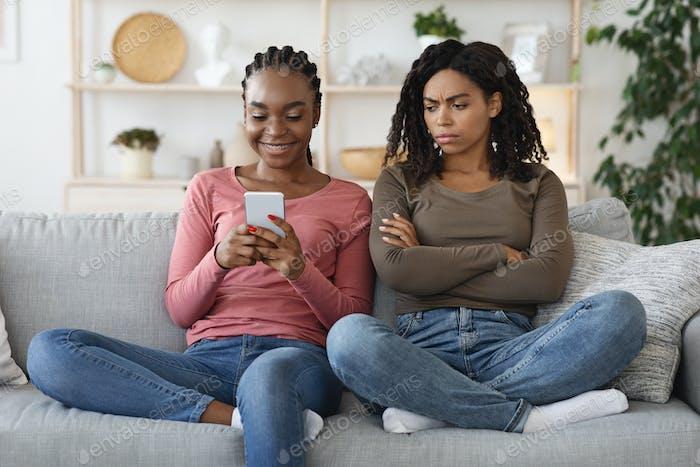 Annoyed black woman looking at girlfriend smartphone screen