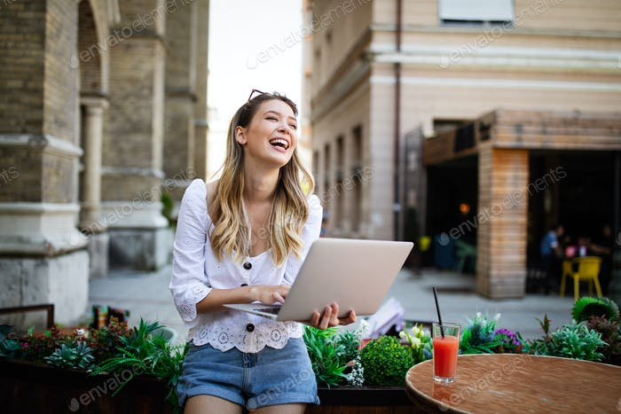 Happy excited woman reading good news on line in a laptop outdoor