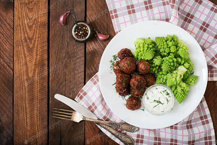 Baked beef meatballs and garnish from boiled cabbage romanesko