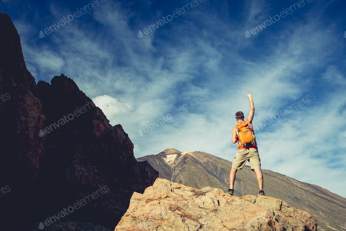 Man celebrating success in mountains, arms outstretched