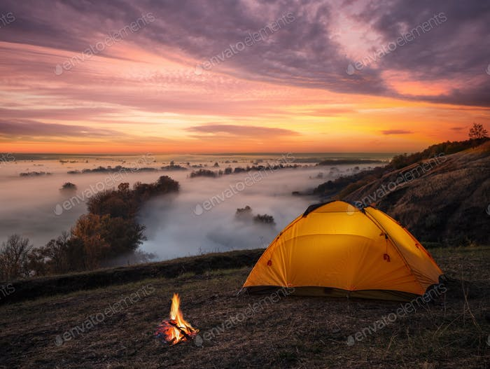 Orange lit inside tent and fire over misty river at sunset
