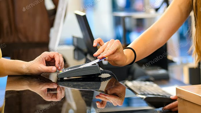 Payment by credit card with contactless technology. Close-up of hands, unrecognizable people.