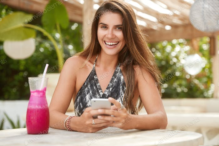 Pretty adorable woman dials telephone number on modern smart phone, enjoys online communication with