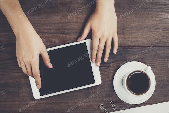 Frauen Hände mit Tablet-Computer und Kaffee auf dem Tisch