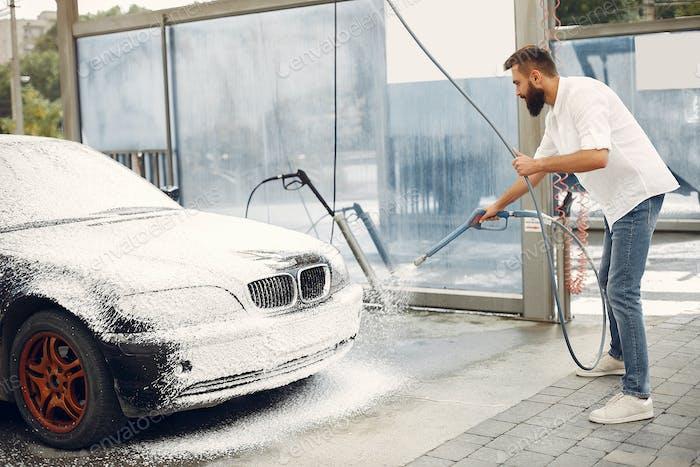Mann wäscht sein Auto in einer Waschstation