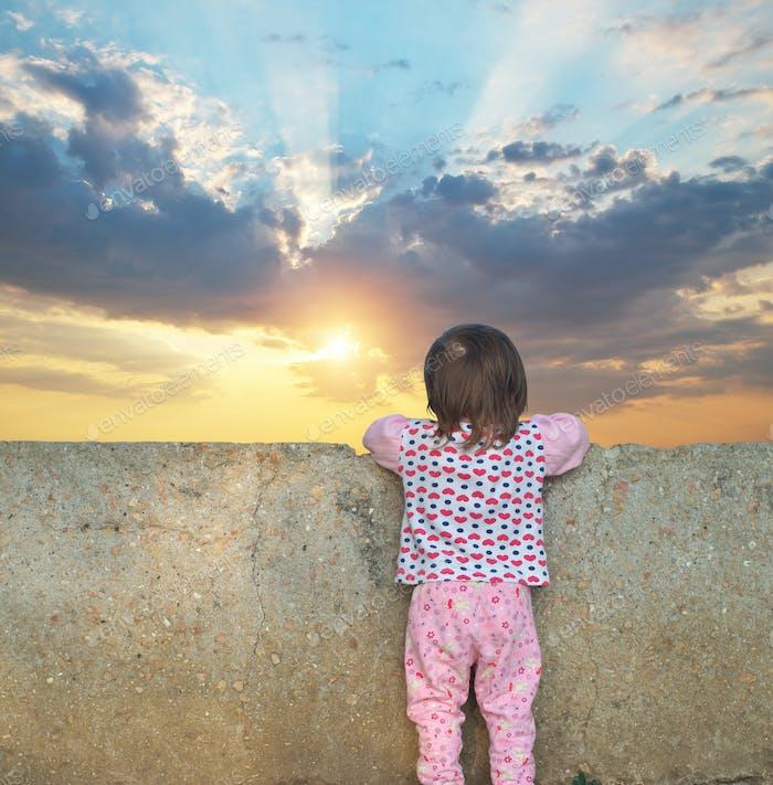 Little girl and sunset sky