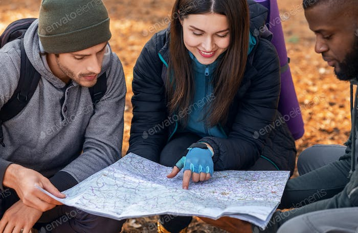 Friends backpackers looking at map in forest