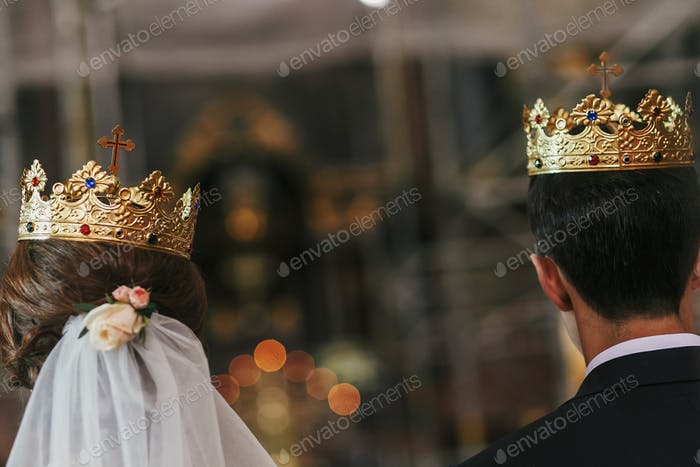 Novia y novio de pie con coronas doradas con cruz