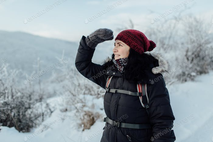 Happy female tourist enjoying snowy country