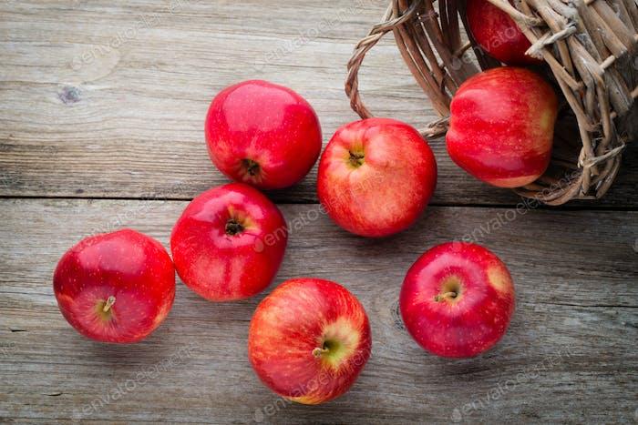 Reife rote Äpfel auf hölzernem Hintergrund.