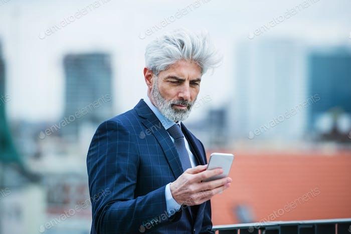A mature businessman standing on a terrace, using smartphone.