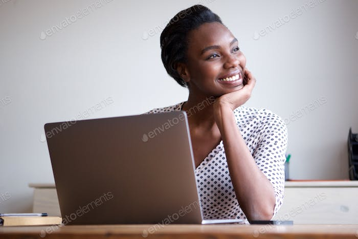Woman resting chin on hand sitting at desk with laptop