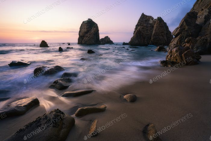 Picturesque coast of Ursa Beach, Sintra, Portugal. Sand beach with rock cliffs lit by sunset evening