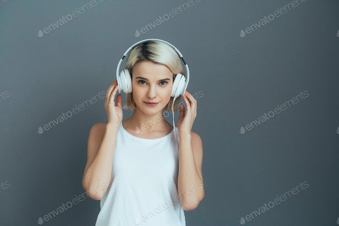 Cute girl in headphones over gray wall