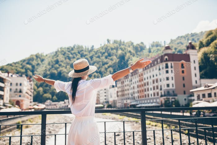 Happy girl at hat on the embankment of a mountain river in a European city