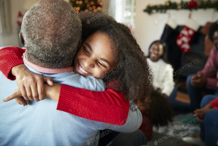 Granddaughter Giving Grandfather Hug As Multi Generation Family Celebrate Christmas At Home