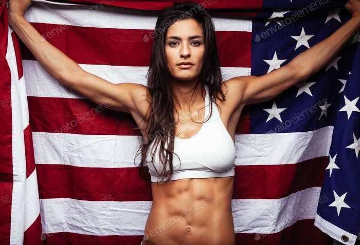 Muscular young woman holding american Flag