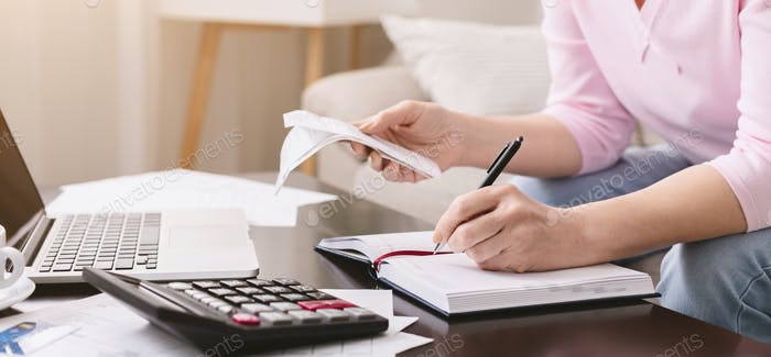 Mature lady with bills noting her purchases at home