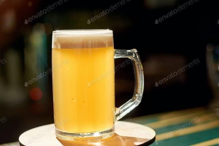 Glass of light beer on bar table