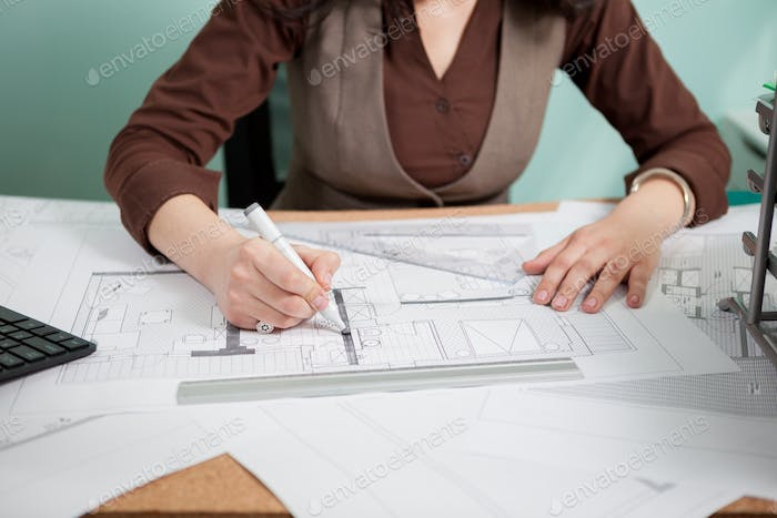 Architect woman at her table drawing on blueprints