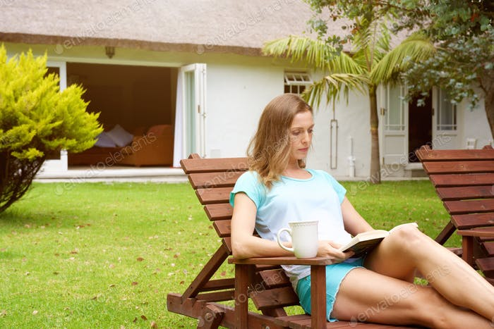Older woman relaxing in home garden with book