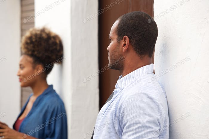 Beautiful man and woman standing apart